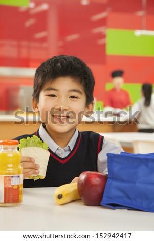 School boy portrait eating lunch in school cafeteria - stock photo