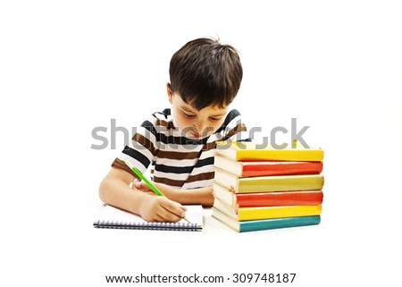 School boy sitting and writing in notebook. Isolated on white background - stock photo