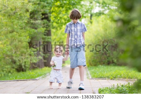 School boy walking with his little sister in a park - stock photo