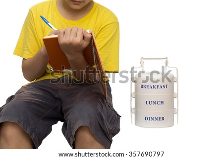 School boy writing a shot note and with food carrier on the side - stock photo