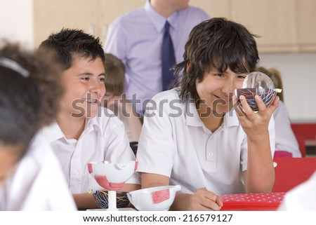 School boys working with biology model in classroom - stock photo