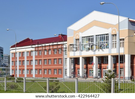 School building. Facade of secondary school. Novokuznetsk, Kemerovo region, Russia. Green lawn and fence around the school. - stock photo