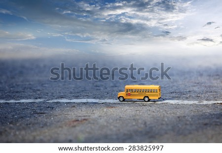 School bus toy model on country road and blue sky. - stock photo