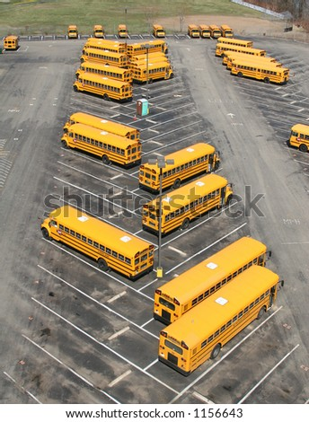 School buses parked in a lot. - stock photo