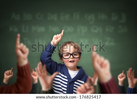 School child with hand raised in the classroom in front of a blackboard with other children concept for teacher's pet, standing out from the crowdand, genius or excelling in education - stock photo