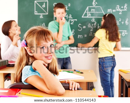 School child with teacher in classroom. - stock photo