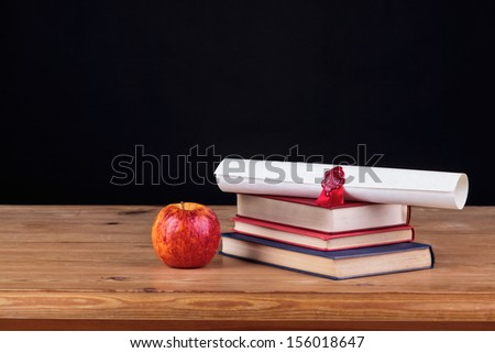 School desk with books and a diploma against a black background, add you own text. - stock photo
