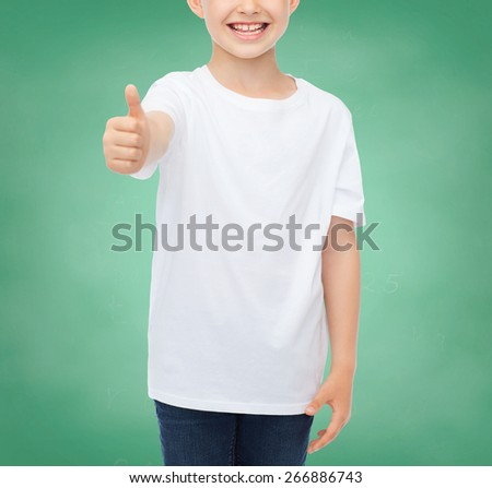 school, education, advertising, people and childhood concept - close up of smiling little boy in white blank t-shirt showing thumbs up over green chalk board background - stock photo