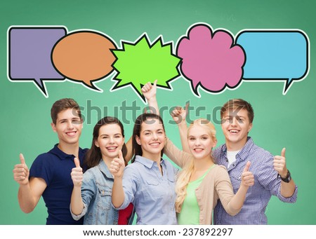 school, education, communication, gesture and people concept - group of smiling teenagers showing thumbs up over green board background with text bubbles - stock photo