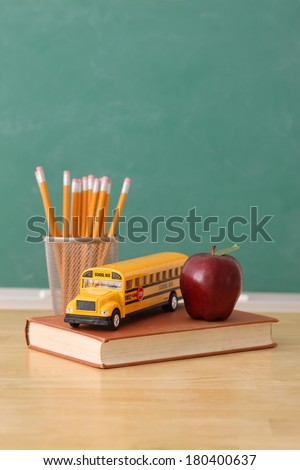 School education still life with pencils, apple, book and toy school bus, chalkboard background - stock photo