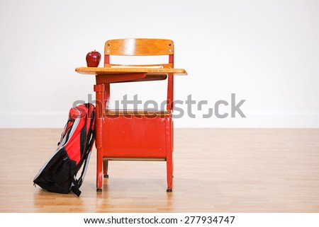 School: Empty School Desk With Apple And Backpack - stock photo