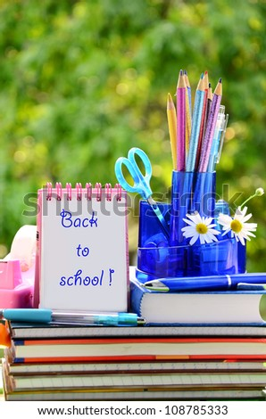 school equipment and notebook empty card with space for text against green trees - stock photo
