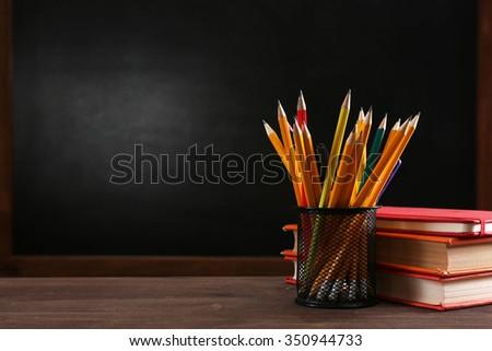 School equipment on desk on blackboard background - stock photo