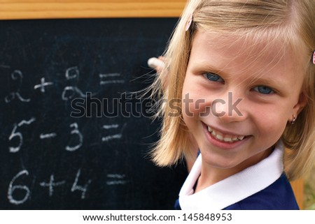school girl doing math problems on the chalkboard - stock photo