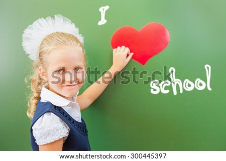 School Girl holding the symbol of heart at the school classroom near the blackboard, there is written - I love school. Very important to teach children to love school. Welcome back to school! - stock photo