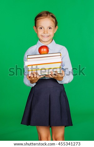 school girl in a school uniform holding a stack of books and red apple.. Learning and school concept. Image on chromakey background. - stock photo