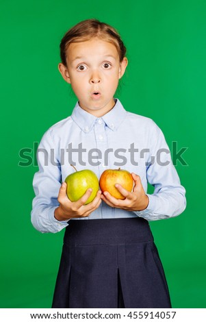 school girl in a school uniform holding two apples. Learning and school concept. Image on chromakey background. - stock photo