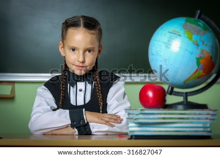 school, girl, schoolgirl 6 years in a black dress and a white shirt with two pigtails on the table Globe and red apple, microscop - stock photo