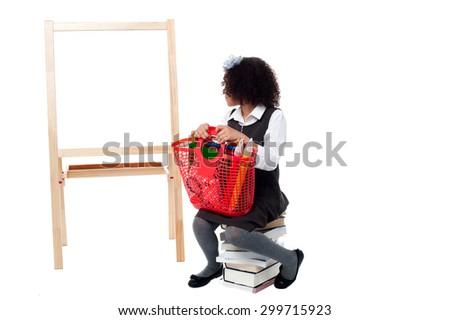 School girl sitting on books, watching the board - stock photo