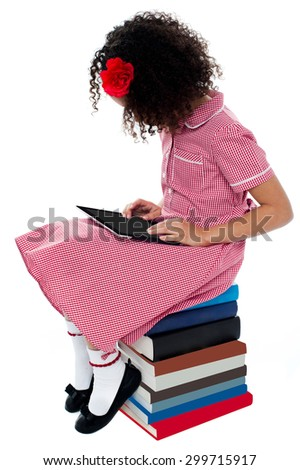 School girl sitting on books with digital tablet - stock photo
