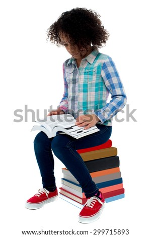 School girl sitting on stack of book and reading - stock photo