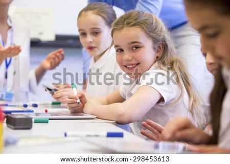 School girl smiles at the camera as she sits at her desk while working. - stock photo