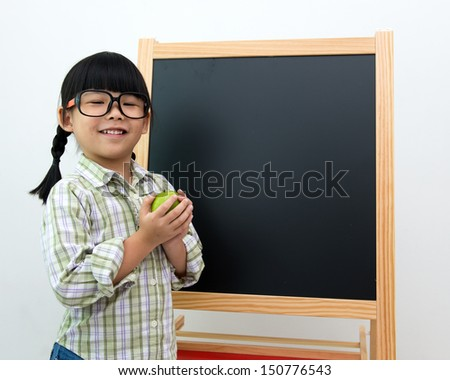 School girl wearing big spectacles posing next to a blackboard - stock photo