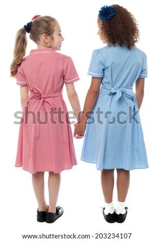 School girls holding hands, rear view shot - stock photo