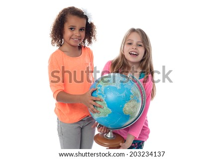 School girls locating countries on globe - stock photo