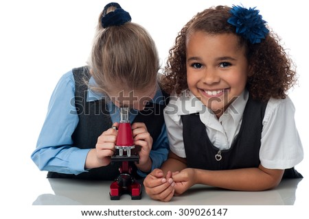 School girls working with a microscope - stock photo