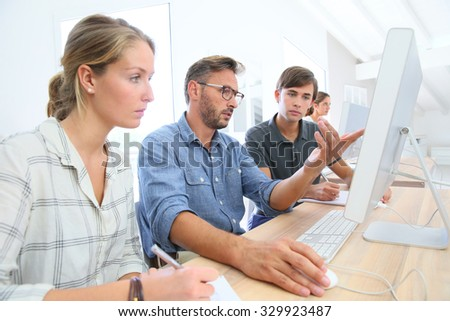School instructor helping students with work project - stock photo