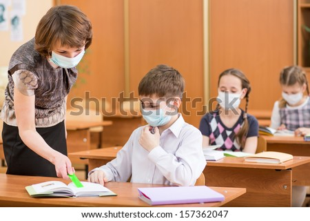 school kids and teacher with protection mask against flu virus at lesson - stock photo