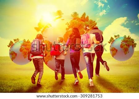 School kids running in school corridor against blue sky over green field - stock photo