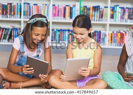School kids sitting on floor using digital tablet in library at elementary school - stock photo
