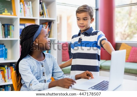 School kids using a laptop in library at school - stock photo