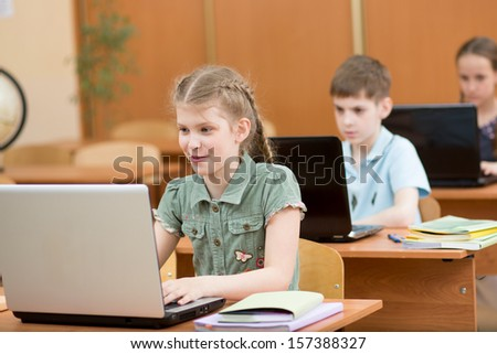 school kids using laptop at lesson - stock photo