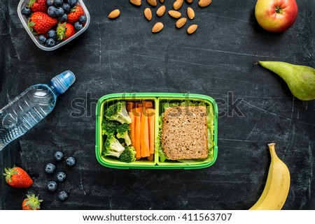 School lunch box with sandwich, vegetables, water, almonds and fruits on black chalkboard. Healthy eating habits concept - background layout with free text space. Flat lay composition (top view). - stock photo