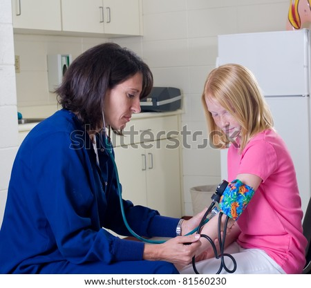 School nurse checking blood pressure of student patient - stock photo