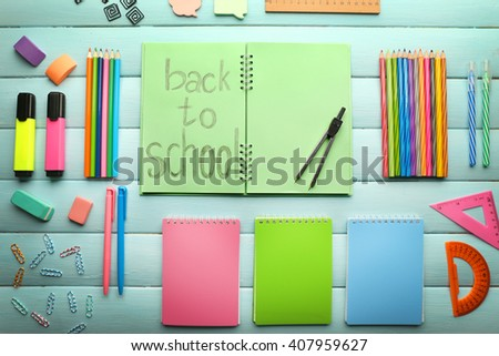 School set with back to school inscription in notebook and stationery on wooden blue background - stock photo