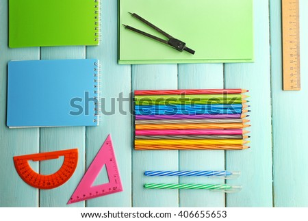 School set with notebooks, rulers and colored pencils on wooden blue background - stock photo