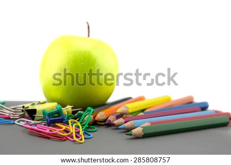 School stationery and apple green on white background - stock photo