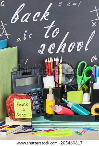 school stationery laid on a background of chalkboard with the words - stock photo