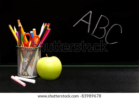 School supplies and apple in front of a blackboard with ABC written in chalk - stock photo