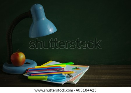 School supplies and blue desk lamp on a wooden surface against a blackboard. A desk lamp, notebooks, handles, colored pencils, rulers and red apple on a wooden table - stock photo