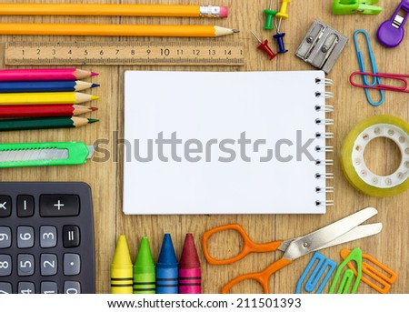 school supplies and checked notebook on wood background - stock photo