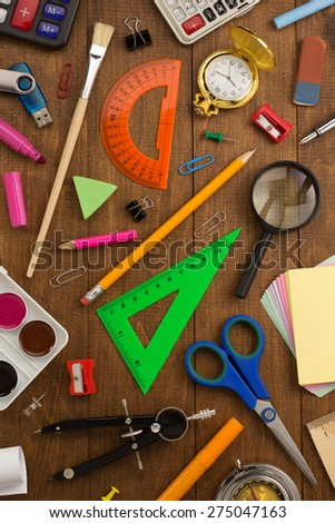 school supplies and notebook on wooden background - stock photo