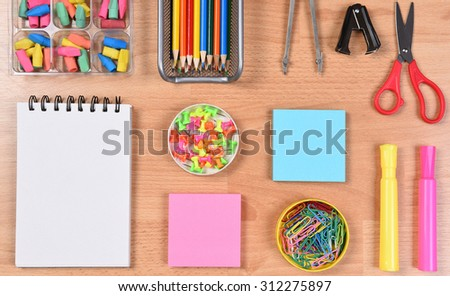 School supplies arranged on a students desk. Closeup overhead view. Back to School concept. - stock photo