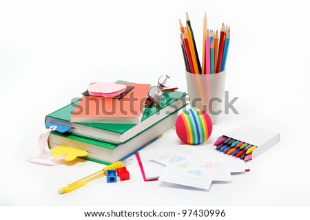 School supplies: books, notebook, pens, pencils, glasses, an apple on a white background. - stock photo