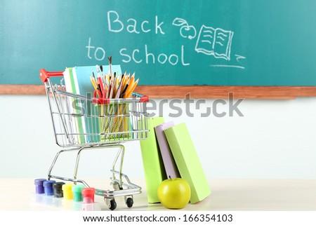 School supplies in supermarket cart on blackboard background  - stock photo