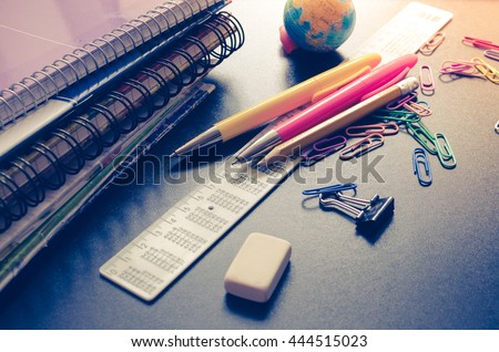 School supplies on blackboard background. Back to school concept with stationery. Notebook stack, pens and pencil. Schoolchild and student studies accessories. Back to school concept. Toned image. - stock photo